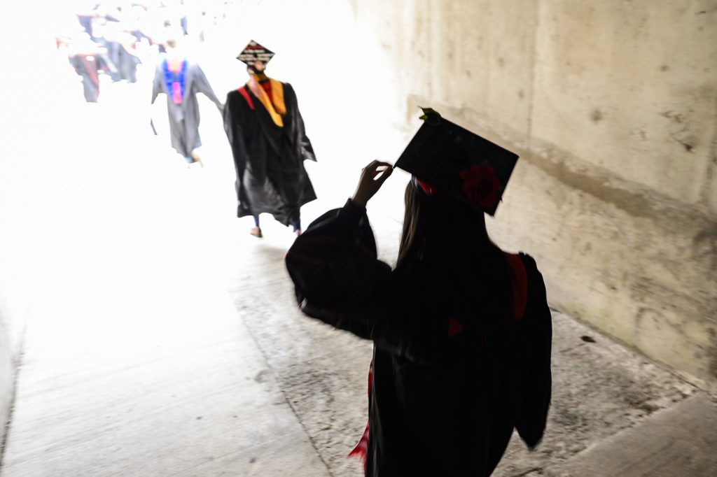 A graduate adjust their mortarboard while walking through a tunnel into Camp Randall Stadium at the University of Wisconsin-Madison during UW-Madison's spring commencement ceremony on May 12, 2018. The outdoor graduation was attended by more than 6,500 bachelor's and master's degree candidates, and their guests. (Photo by Jeff Miller/UW-Madison)
